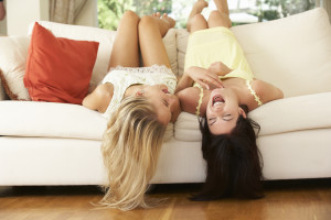 Two Female Friends Lying Upside Down On Sofa